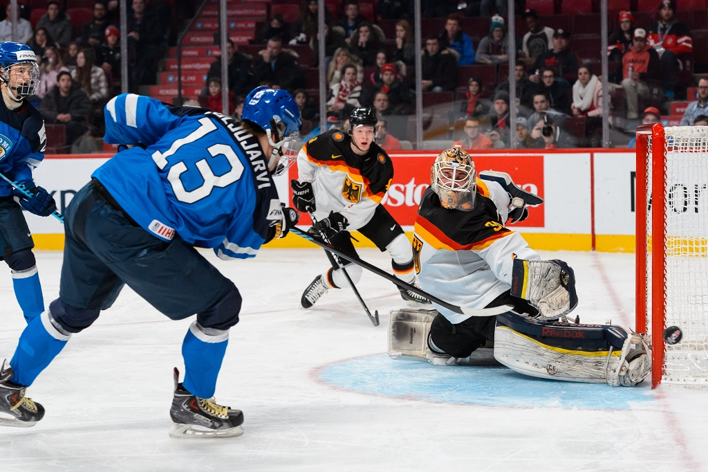 MONTREAL, QC - DECEMBER 31: Kevin Reich #30 of Team Germany stops a shot by Jesse Puljujarvi #13 of Team Finland in a preliminary round game during the 2015 IIHF World Junior Hockey Championships at the Bell Centre on December 31, 2014 in Montreal, Quebec, Canada. Team Finland defeated Team Germany 2-0