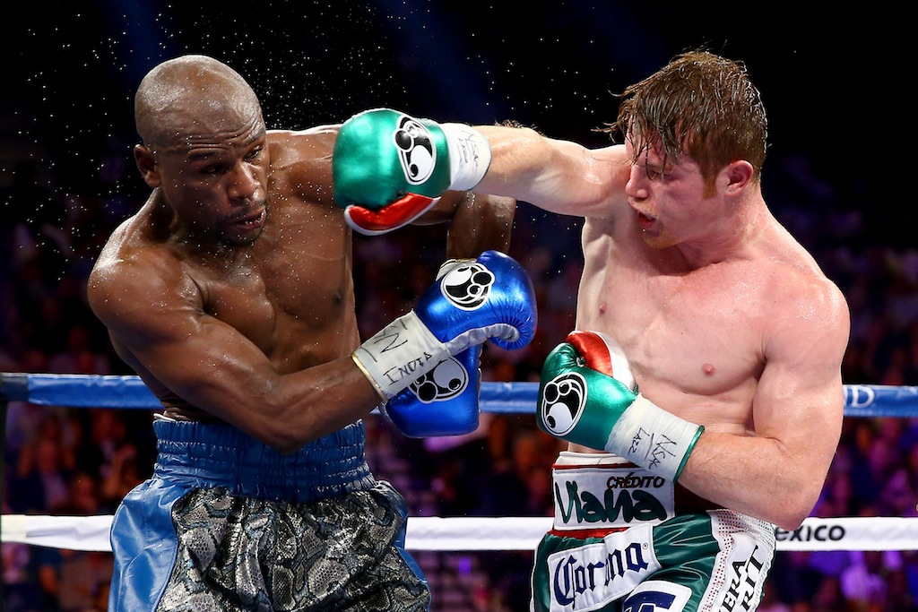 Al Bello/Getty Images (R-L) Canelo Alvarez throws a right at Floyd Mayweather Jr. during their WBC/WBA 154-pound title fight