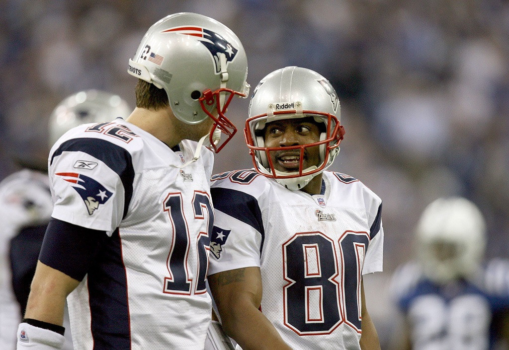 Tom Brady and Troy Brown talk as they walk off the field.