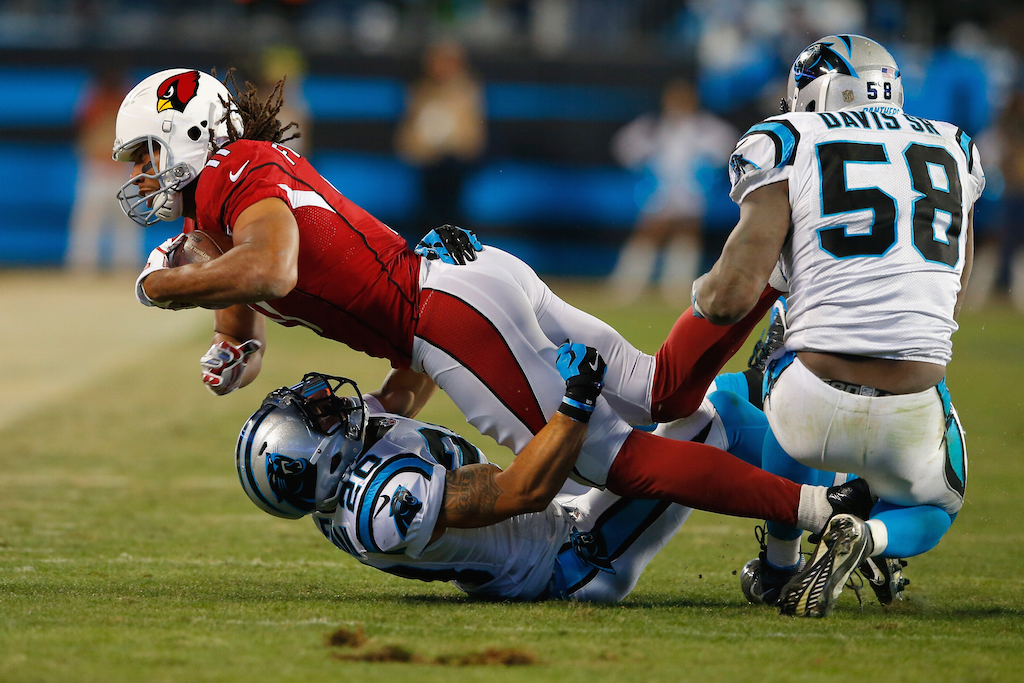 Thomas Davis #58 helps tackle Larry Fitzgerald