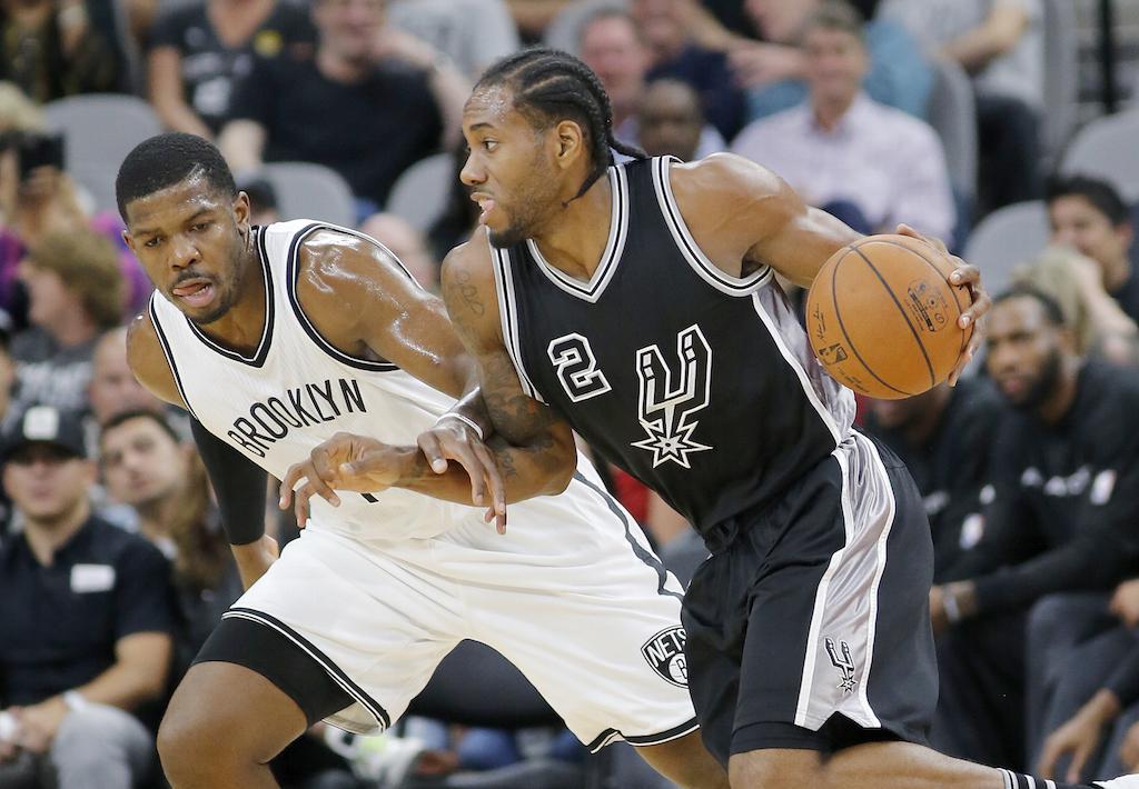 Kawhi Leonard #2 of the San Antonio Spurs drives around Joe Johnson #7