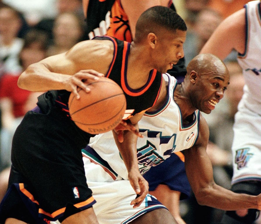 Jacque Vaughan (back) of the Utah Jazz fights through a pick set for Kevin Johnson of the Phoenix Suns