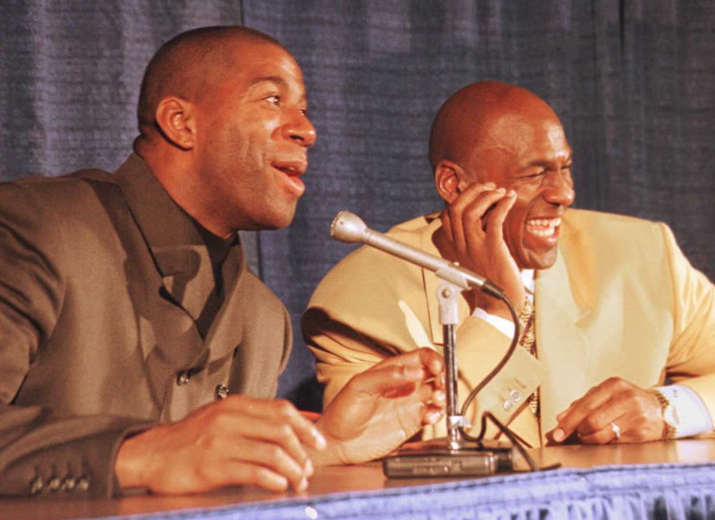 Los Angeles Lakers Earvin 'Magic' Johnson and Michael Jordan (R) of the Chicago Bulls laugh with a reporter.
