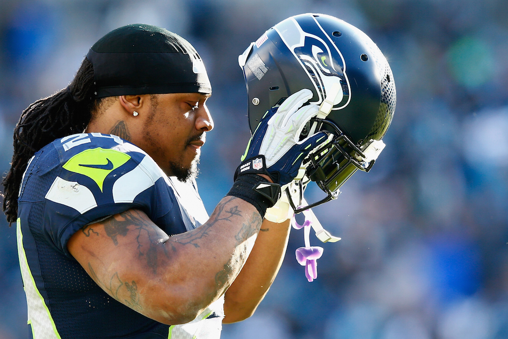 Marshawn Lynch removes his helmet and cools off after a play.