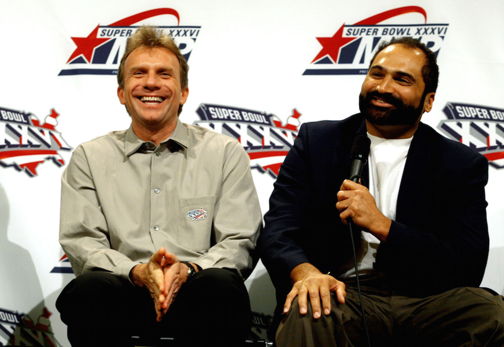 Joe Montana and Franco Harris laugh at a press conference for former Super Bowl MVP's