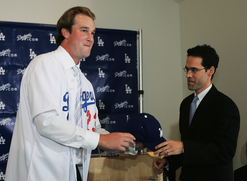 LOS ANGELES - JANUARY 12:  Right handed pitcher Derek Lowe (L) receives a hat from General Manager Paul DePodesta during a press conference after signing a four-year contract with the Los Angeles Dodgers January 12, 2005 at Dodger Stadium in Los Angeles, California.