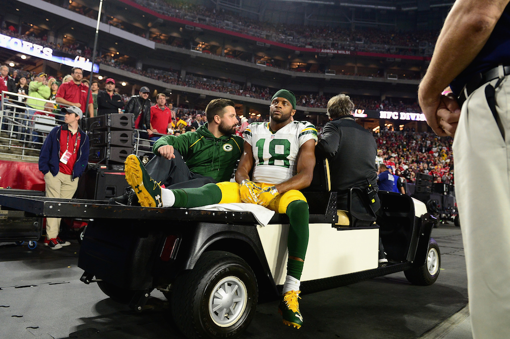 Randall Cobb is carted off the field after being injured