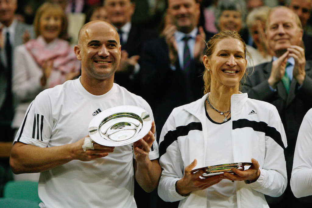 Andre Agassi and Steffi Graf look on with their commemorative trophies following the 'Centre Court Celebration' at Wimbledon