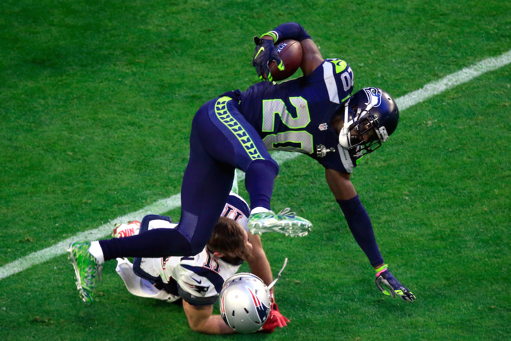 Julian Edelman #11 of the New England Patriots tackles Jeremy Lane #20 of the Seattle Seahawks after an interception in the first quarter during Super Bowl XLIX