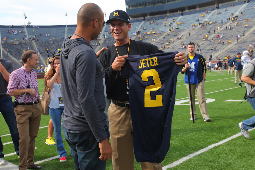 Head coach Jim Harbaugh (R) of the Michigan Wolverines presents baseball great Derek Jeter (L) of the New York Yankees with a jersey