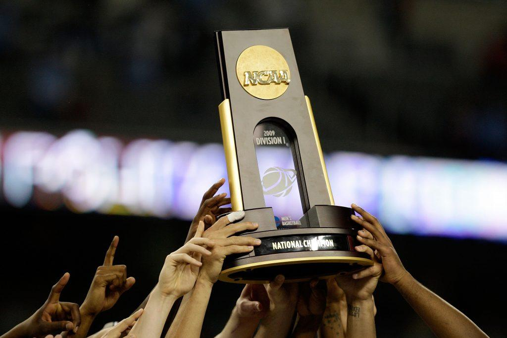 The NCAA National Championship trophy is hoisted in the air.