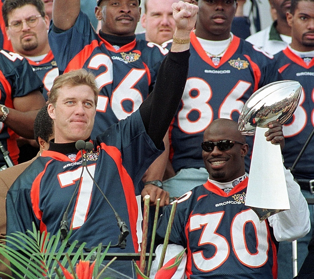 DENVER, CO - 27 Jan 1998: Denver Broncos quarterback John Elway (L) salutes the crowd while Super Bowl MVP Terrell Davis holds the Vince Lombardi Trophy during a rally and victory parade 27 January at the City and County Building in Denver Colorado. Thousands attended the celebrations for the Broncos' victory over the Green Bay Packers in Super Bowl XXXII. (Photo credit should read DOUG COLLIER/AFP/Getty Images)