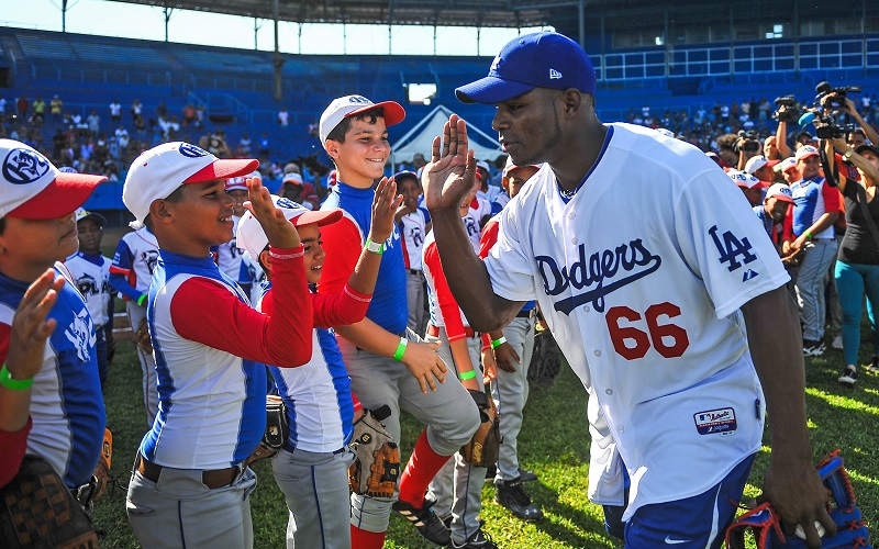 MLB player Yasiel Puig shakes hands with Cuban children at the Latin American Stadium in Havana, Cuba.