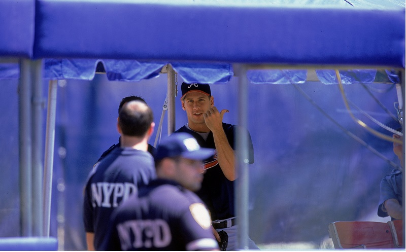 Pitcher John Rocker of the Atlanta Braves waits with his NYPD escort during a game against the New York Mets.