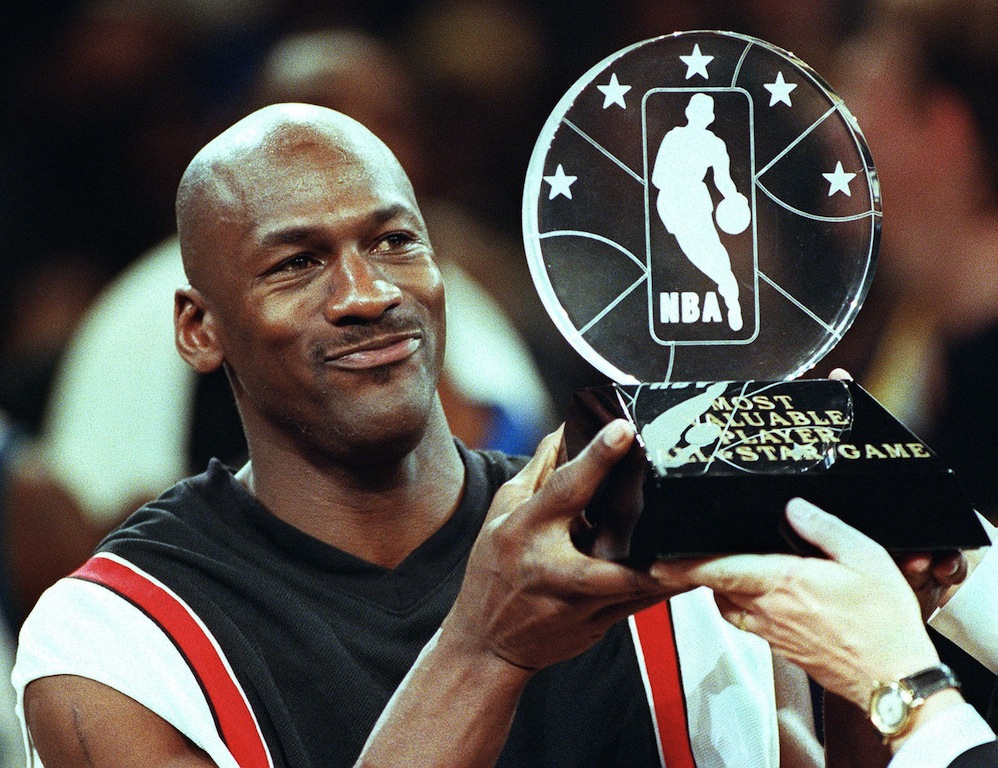 Michael Jordan holds his All-Star game MVP trophy.