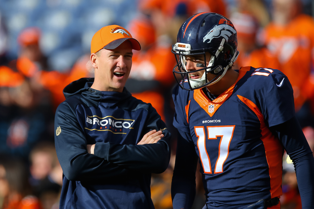 DENVER, CO - DECEMBER 13: Injured quarterback Peyton Manning of the Denver Broncos, left, has a word with quarterback Brock Osweiler #17 as players warm up before a game against the Oakland Raiders at Sports Authority Field at Mile High on December 13, 2015 in Denver, Colorado