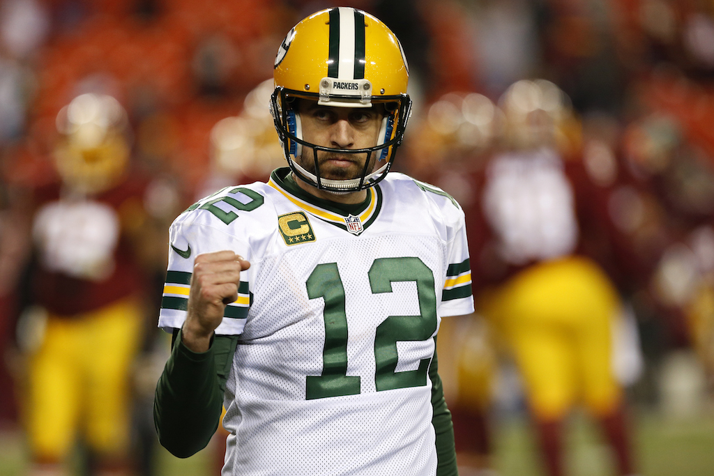 Aaron Rodgers fist pumps after throwing a touchdown pass.