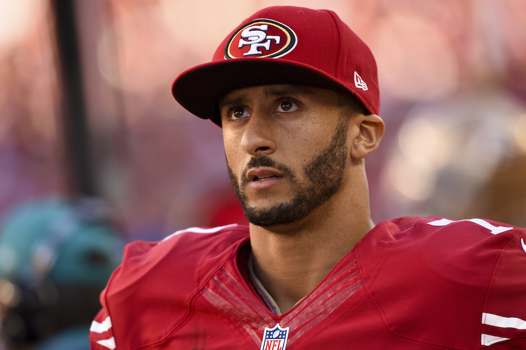 Colin Kaepernick stands on the sidelines during a game.