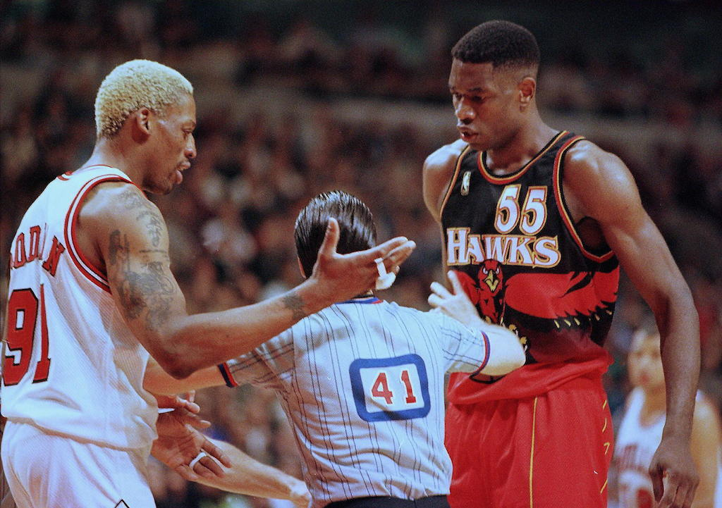 A referee attempts to separate Dennis Rodman (L) and Dikembe Mutombo.
