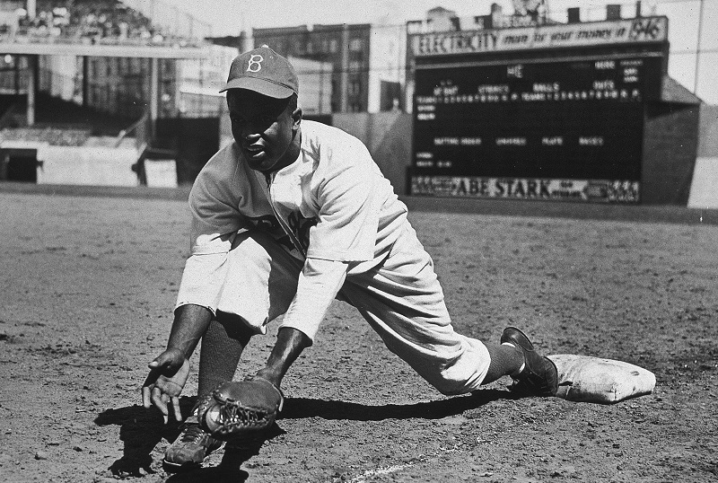 American baseball player Jackie Robinson (1919 - 1972) grounds a ball at first place while warming up for an exhibition game against the New York Yankees, Ebbets Field, NYC, 1950s. (Photo by Hulton|Archive/Getty Images)