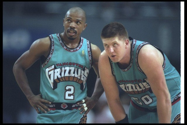 Vancouver's Greg Anthony (L) and Bryant Reeves look on during a game against the Clippers.