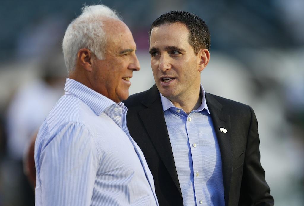 Philadelphia Eagles owner Jeffrey Lurie (L) speaks with Howie Roseman. | Rich Schultz/Getty Images