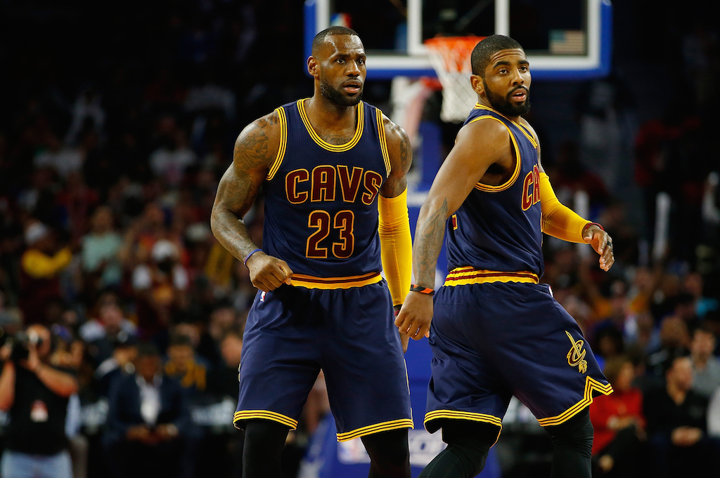 LeBron James and Kyrie Irving stand on the court next to each other.