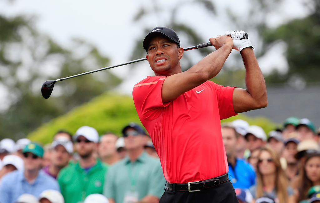 Tiger Woods is swinging as he plays golf.