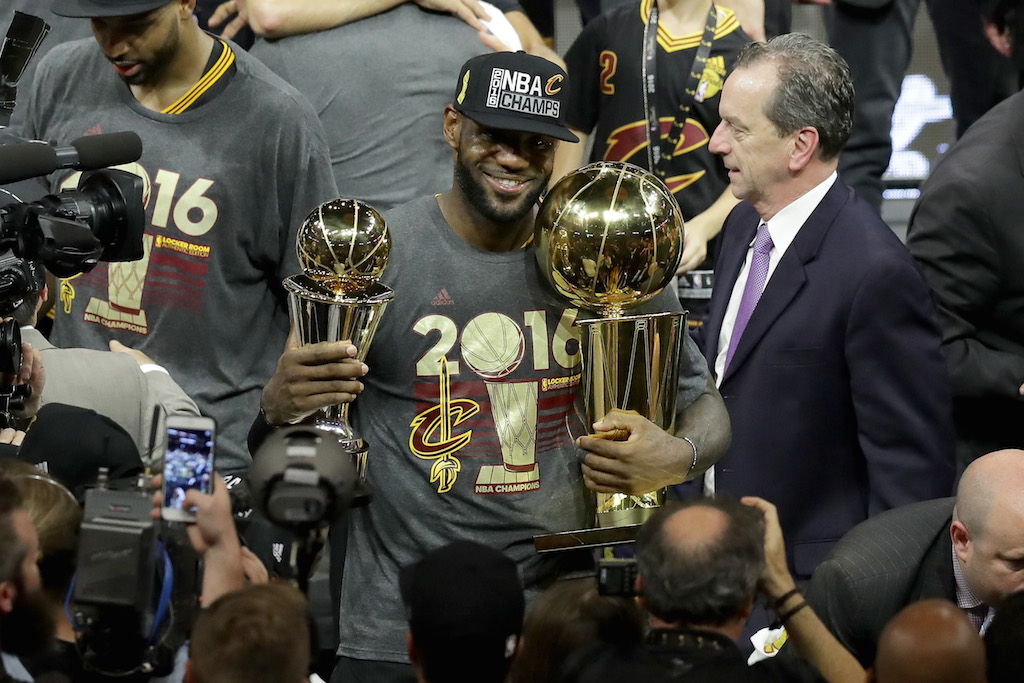LeBron James holds the Larry O'Brien Championship Trophy and the Bill Russell NBA Finals MVP. | Ronald Martinez/Getty Images