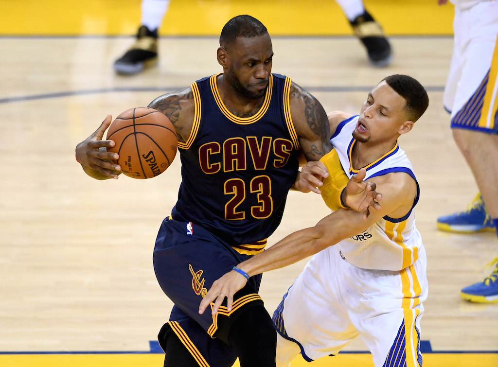 LeBron James looks to drive past Stephen Curry.