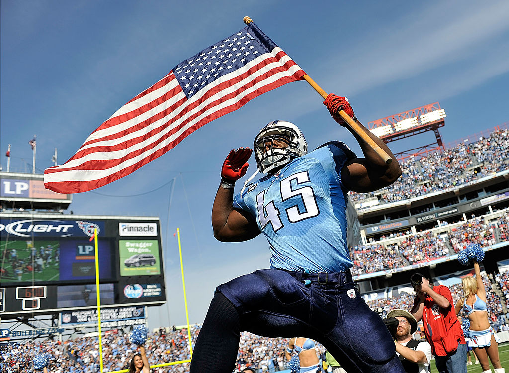 Armed services veteran Ahmard Hall (of the Tennessee Titans) brings out the American flag before a game.