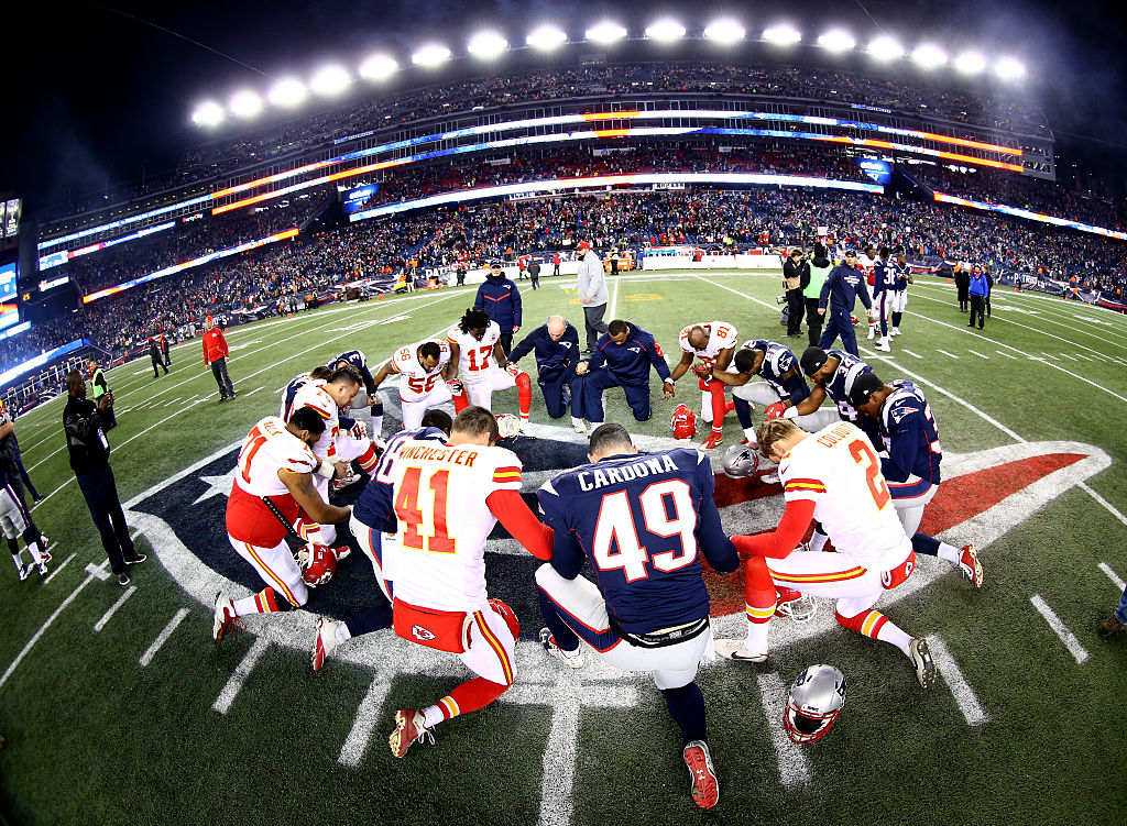 Players from the Kansas City Chiefs and New England Patriots, including No. 49 Joe Cardona, gather at mid-field after the AFC Divisional Playoff Game in 2016.