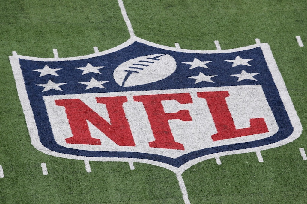 The NFL logo on the field.