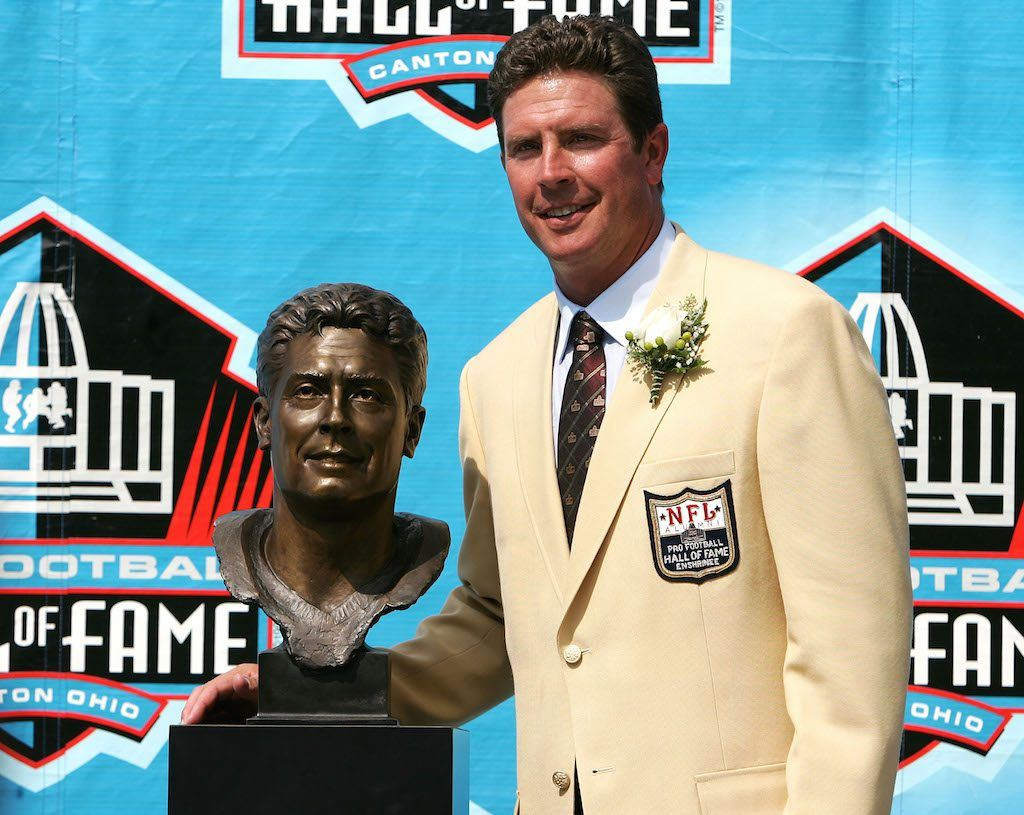 Dan Marino poses next to his Hall of Fame bust.