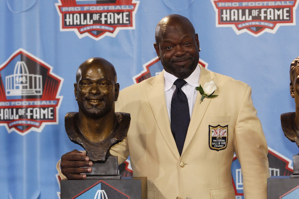 Emmitt Smith stands next to his bust during a Hall of Fame induction ceremony.