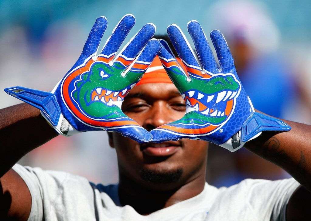 A Gators football player holds up his gloves, which have alligators on them.