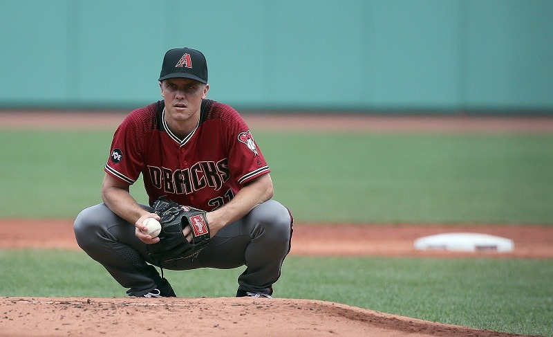 Zack Greinke crouches down on the mound.