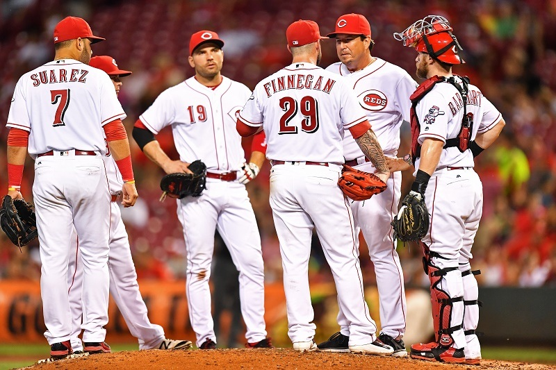 The Cincinnati Reds stand on the mound.