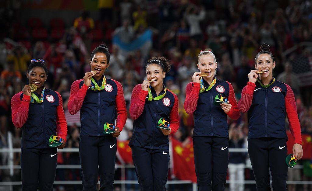 Gold Medalists Simone Biles, Gabrielle Douglas, Lauren Hernandez, Madison Kocian and Alexandra Raisman of the United States celebrate on the podium at the medal ceremony for the Artistic Gymnastics Women's Team.