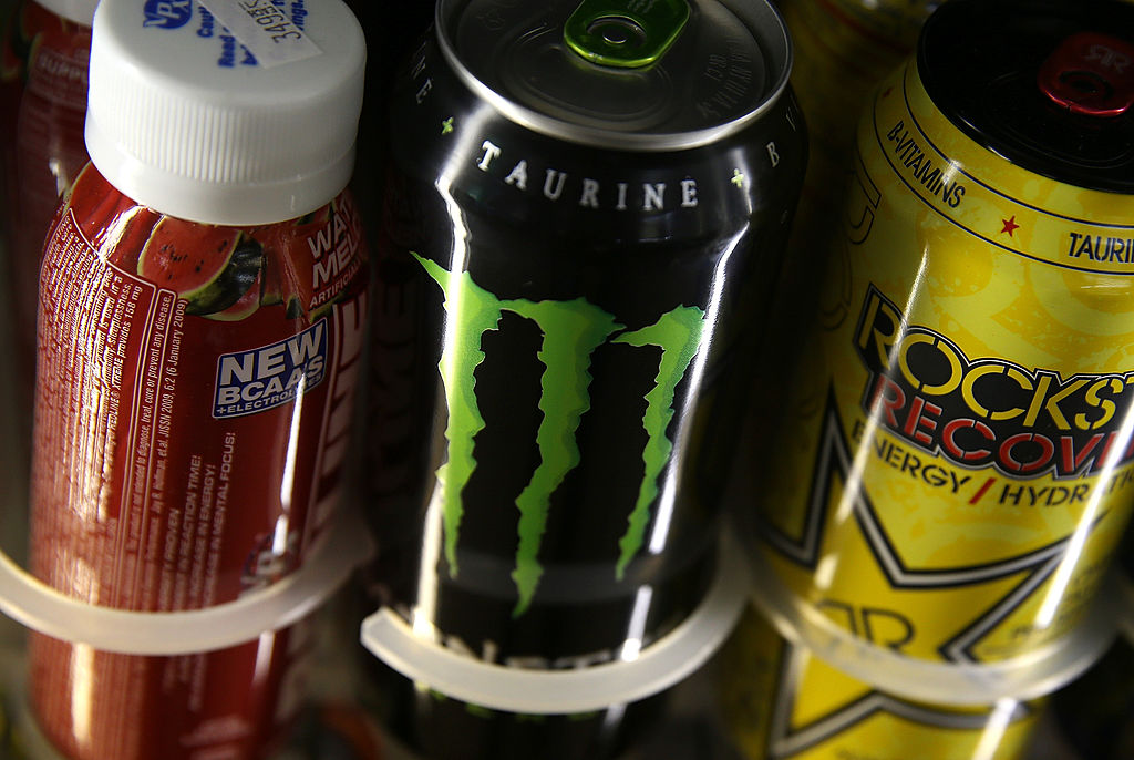 Cans of energy drinks are displayed on a shelf at a convenience store.