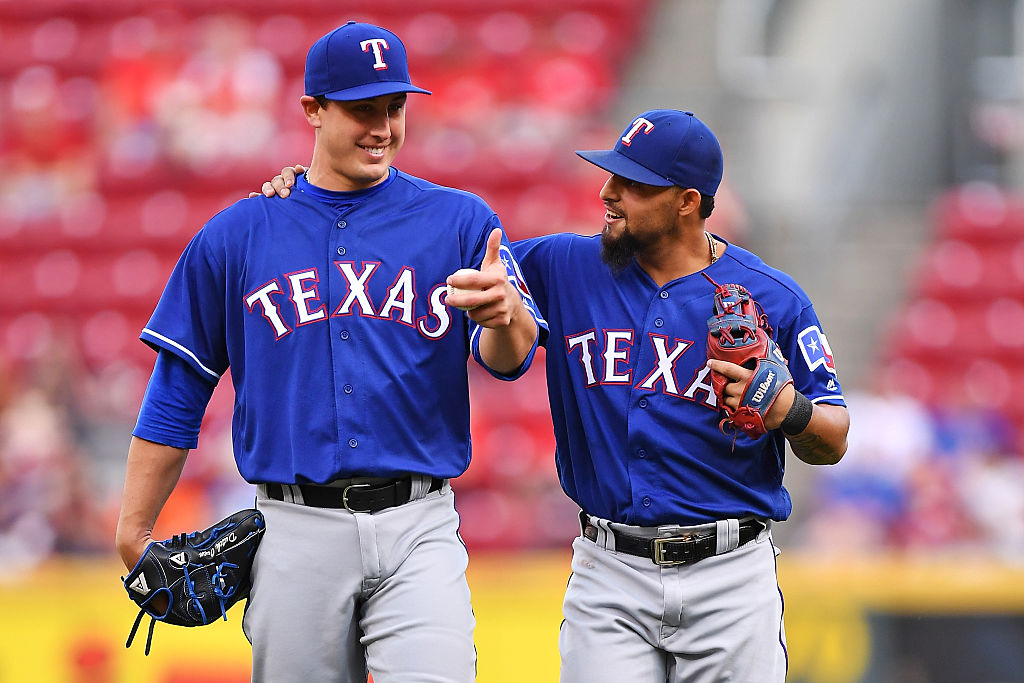 Derek Holland and Rougned Odor smile as they walk off the field.