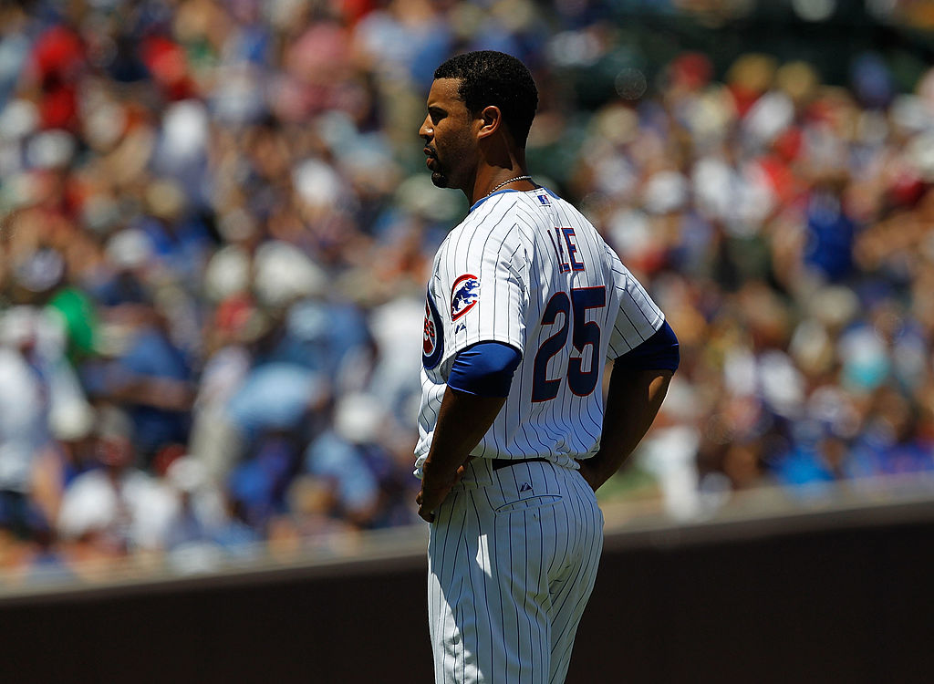 Derrek Lee of the Chicago Cubs stands and waits for a teammate to bring him his hat and glove after flying out to end an inning against the Cincinnati Reds at Wrigley Field on July 3, 2010 in Chicago, Illinois. The Cubs defeated the Reds 3-1.