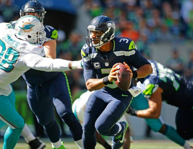 Russell Wilson tries to evade the Dolphins' rush.