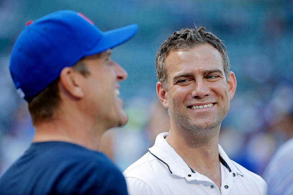 Theo Epstein (R), President of Operations for the Chicago Cubs, talks with head football coach Jim Harbaugh of the University of Michigan before the game between the Chicago White Sox and the Chicago Cubs at Wrigley Field on July 27, 2016 in Chicago, Illinois. | Jon Durr/Getty Images