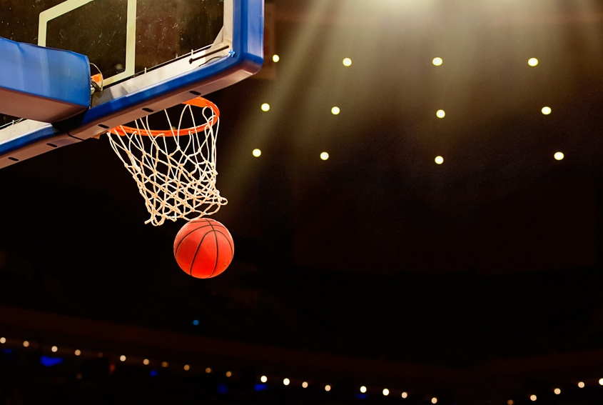 A ball swishes through the net at a basketball game