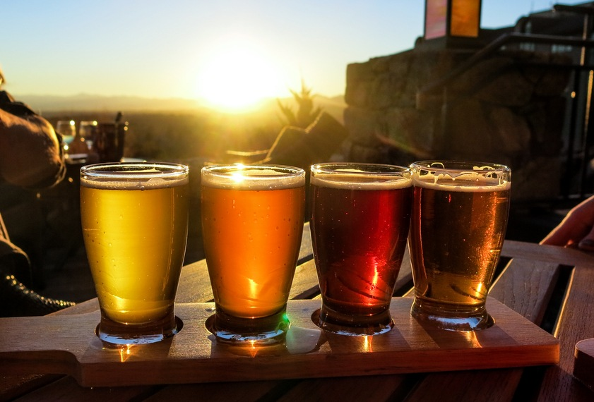 A colorful beer flights is illuminated against a bright sunset.