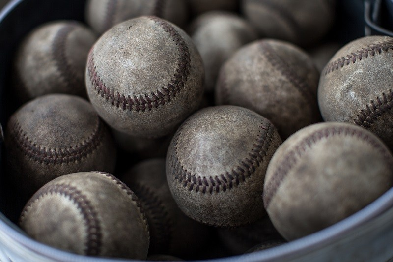 Used baseballs in a bucket