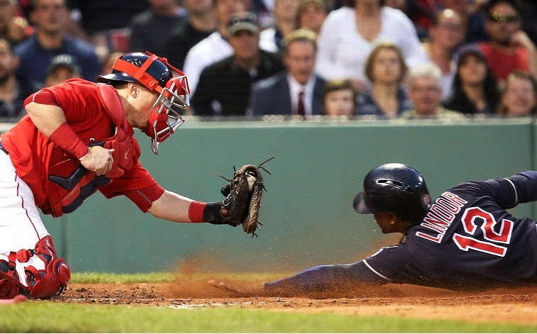 Francisco Lindor of the Cleveland Indians slides under the tag of Christian Vazquez of the Boston Red Sox during a 2016 game.