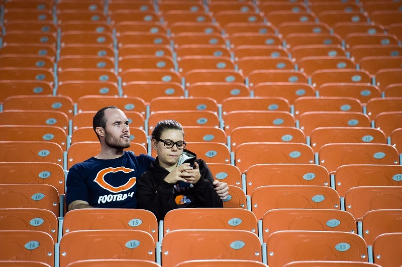 A Chicago Bears fan and a Cleveland Browns fan wait out the end of a game.