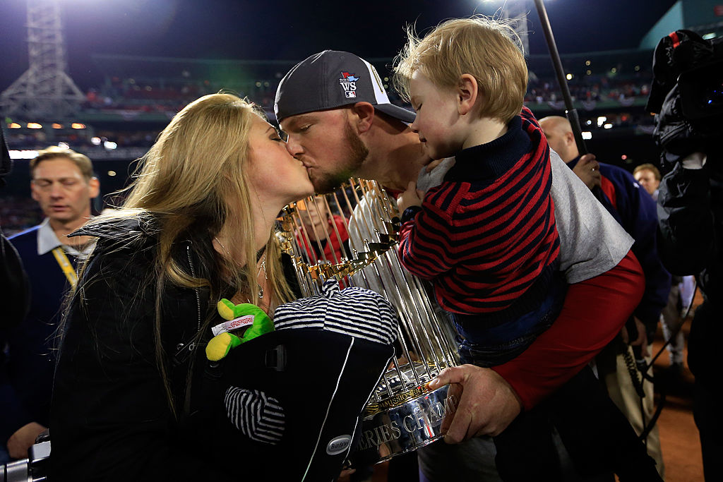 Jon Lester #31 of the Boston Red Sox celebrates with his son Hudson and wife Farrah Stone Johnson after defeating the St. Louis Cardinals 6-1 in Game Six of the 2013 World Series at Fenway Park on October 30, 2013 in Boston, Massachusetts.
